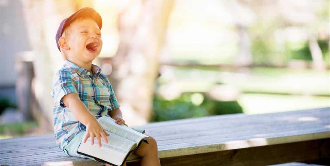 Kid Laughing While Reading Bible About Servant Leadershiip